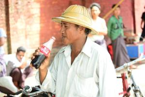 Man Enjoys Coca-Cola in Myanmar. Photo: The Coca-Cola Company.