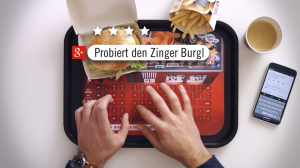 KFC Germany's Bluetooth tray liner. Translation: Try the zinger burger. Credit: photo from KFC video.